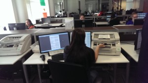 An Ancestry team member feeds pages of genealogical data into a high-speed scanner.